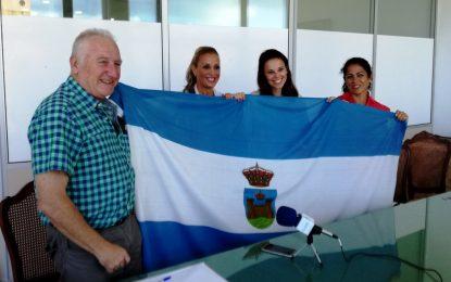 Helenio Lucas Fernández  entrega la bandera de la ciudad a las tres deportistas que participarán en la Media Maratón de Lisboa